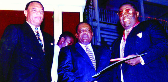 Kenneth Francis C. B. E.  recieving an award from Former Prime Minister Rt. Hon. Hubert Ingraham at the 25th Anniversay of independence. Current Prime Minister Rt. Hon. Perry G. Christie looks on.