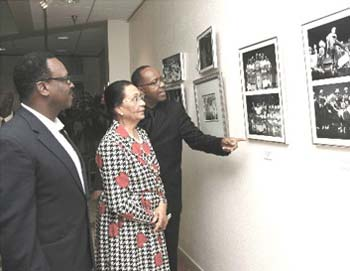 HE Governor General Dame Marguerite Pindling, Minister of Youth, Sports and Culture the Hon. Dr. Daniel Johnson, and Choir Director Cleophas Adderley view the historical display of photographs depicting the development of the Bahamas National Youth Choir over 25 years at its anniversary exhibit at the Central Bank of The Bahamas.