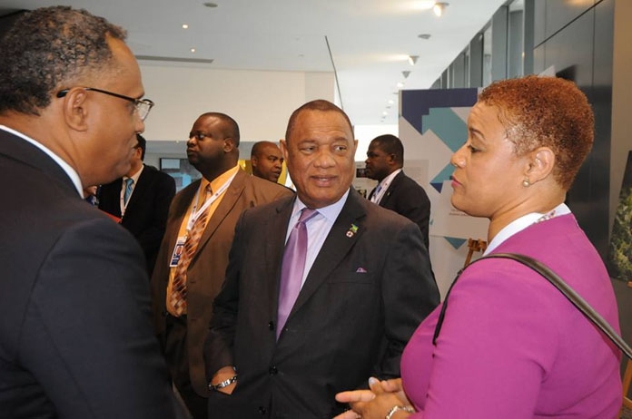 Ministers Strachan and Darville engaged in conversation with Prime Minister