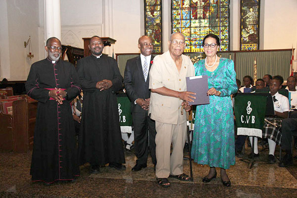 Certificate Presentation Photo shows Her Excellency Dame Marguerite Pindling, right, presenting certificate to Roosevelt Godet.  Minister of Tourism Obie Wilchcombe is centre; and the Dean Very Reverend Patrick Adderley and Fr. Humes.