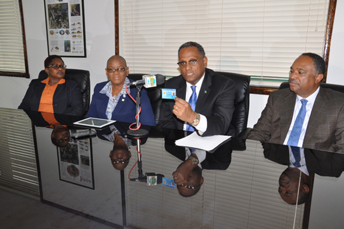 Minister for Grand Bahama, the Hon. Dr. Michael Darville holds up a new NIB smart card. He is encouraging all residents on Grand Bahama, and indeed throughout the country to register for the NIB card. Left to right in the photo are: Rosetta Booth, Chief Operation Manager at NIB's Freeport office; Cecile Williams-Bethel, Senior Deputy Director of Operations, NIB; Dr. Darville; and Melvin Seymour, Permanent Secretary, Ministry for Grand Bahama. (BIS Photo/Vandyke Hepburn)