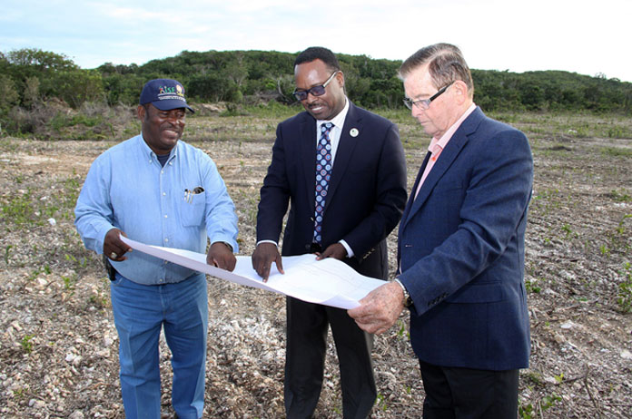 The Hon. Daniel Johnson, Minister of Youth, Sports and Culture (centre) and the Hon. Edison Key, MP for Central and South Abaco look over plans for the Sporting Complex underway in Moore's Island.
