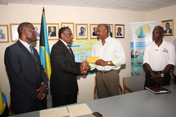 "Minister of Agriculture and Marine Resources the Hon. V. Alfred Gray, second left, makes cheque presentation to organizer of the ""King Eric"" Gibson All For One Regatta -- Eric Gibson, Jr., January 4, 2016 at the Ministry of Agriculture and Marine Resources."