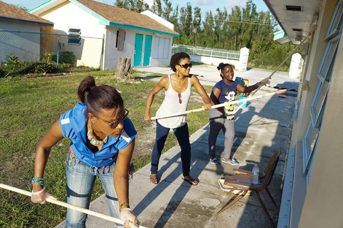 Simms Primary School Head Girl Knia Adderley helps paint her school.