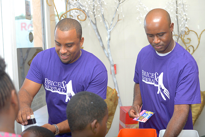 Hard at work: A Sure Win and Brice & Newball Foundation co-founders, Leander Brice and Garvin Newball hand out tickets to young party-goers. Pictured: Garvin Newball (L), Leander Brice (R)
