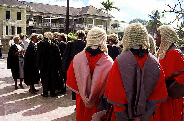A group of male and female judges and lawyers, wearing traditional Bahamian court attire, gather outside a building. --- Image by © Kit Kittle/CORBIS