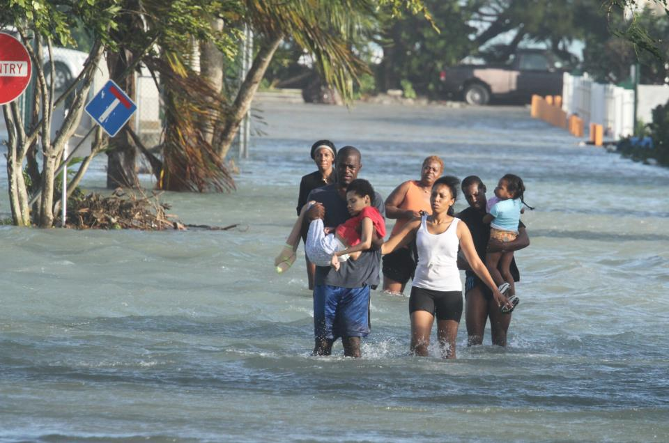 A family in West Grove had to be rescued as their home flooded with water in the aftermath of Hurricane Sandy. Bahamas Press warned Bahamians in low areas to make their way to Hurricane Shelters and avoid being trapped in flood zones.