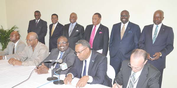 Left to right in the photo seated are: Bradford Wildgoose, Ministry for Grand Bahama; Sanford Culmer, SRA Construction; the Hon. Arnold Forbes, Minister of State in the Ministry of Works and Urban Development; the Hon. Dr. Michael Darville, Minister for Grand Bahama; Colin Higgs, Permanent Secretary, Ministry of Works and Urban Development. Standing left to right: the Hon. V. Alfred Gray, Minister of Agriculture and Marine Resources; the Hon. Dr. Perry Gomez, Minister of Health; the Hon. Obie Wilchcombe, Minister of Tourism; Prime Minister and Minister of Finance, the Rt. Hon. Perry Gladstone Christie; the Hon. Kenred Dorsett, Minister of the Environment and Housing; and the Hon. D. Shane Gibson, Minister of Labour and National Insurance. (BIS Photo/Vandyke Hepburn)