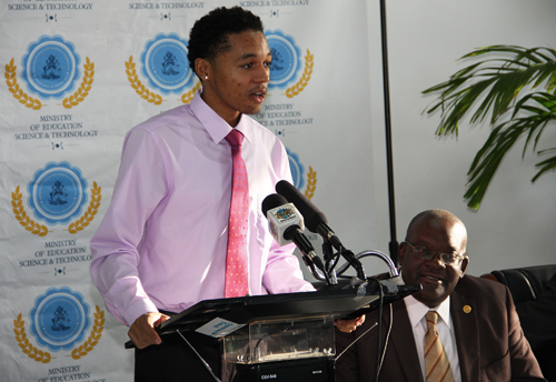 The 2015 All-Bahamas Merit Scholar, Domonic McDonald's response of gratitude for receiving the most coveted award for high school students in the country. Pictured looking on is Reginald Saunders, Administrator Scholarships and Loan Division, Ministry of Education Science and Technology. The awards ceremony was held on Wednesday, August 12, 2105 at the Thomas A. Robinson National Stadium. (BIS Photo/Patrick Hanna).