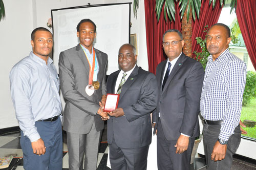 TOKEN OF APPRECIATION -- Deputy Prime Minister and Minister of Works and Development was presented with a plaque by Bahamian track sensation, Jeffrey Gibson during the 2015 GB Annual Meeting and Workshop Luncheon at Ruby Swiss Restaurant on Thursday. Shown from left are: Remington Wilchcombe, President of the Northern Branch of the Bahamas Society of Engineers; Jeffrey Gibson; Deputy Prime Minister Davis; Minister for Grand Bahama, the Hon. Dr. Michael Darville; and DeCosta Bethel, National President of the Bahamas Society of Engineers. (BIS Photo/Andrew Miller)