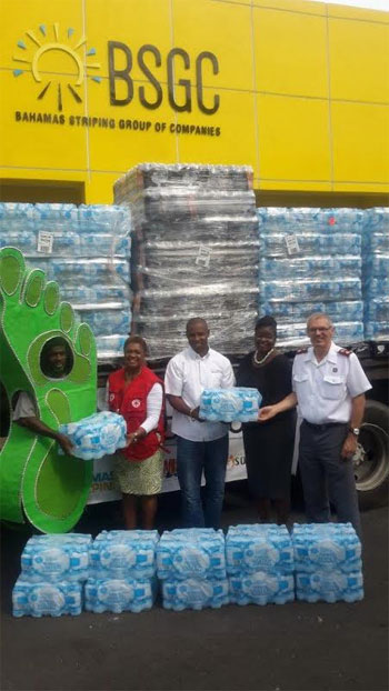 The Bahamas Red Cross and The Salvation Army accept 20,000 bottles of water from The Bahamas Striping Group of Companies. From Left to Right, Bahamas Striping Mascot, Mrs. Jan Mackey, HR & Logistics Manager, Mr. Atario Mitchell, President of Bahamas Striping Group of Companies, Mrs. Delicia Armbrister, Administrative Assistant, The Salvation Army, and Major Clarence Ingraham, Divisional Commander of The Salvation Army