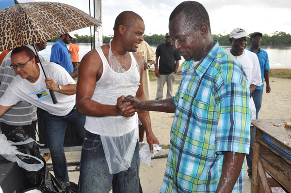 CONGRATULATIONS – Following a highly competitive conch cracking competition on Monday in McLean's Town at the 43rd annual Conch Cracking Competition, Cardinal McIntosh (plaid shirt) is seen congratulating the winner, Joseph Tate. McIntosh, who placed third, was the winner in last year's competition. (BIS Photo/Vandyke Hepburn)