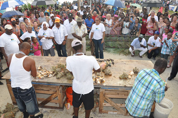 JUDGING THE COMPETITION – Hundreds gathered around the table as the Conch Cracking Competition took place during the 43rd annual festival in McLean's Town on Monday. Shown are Deputy Leader of the Official Opposition and Member of Parliament for East Grand Bahama, Peter Turnquest; Permanent Secretary for the Ministry of Tourism, Harrison Thompson; and former Member of Parliament for High Rock Constituency, Kenneth Russell, the three judges for the event. (BIS Photo/Vandyke Hepburn)