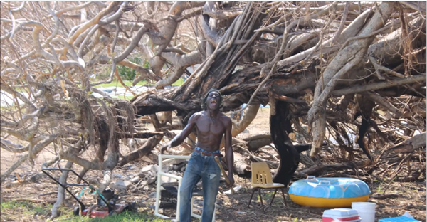 Man on Crooked Island standing in front of an uprooted tree following the passage of Hurricane Joaquin.