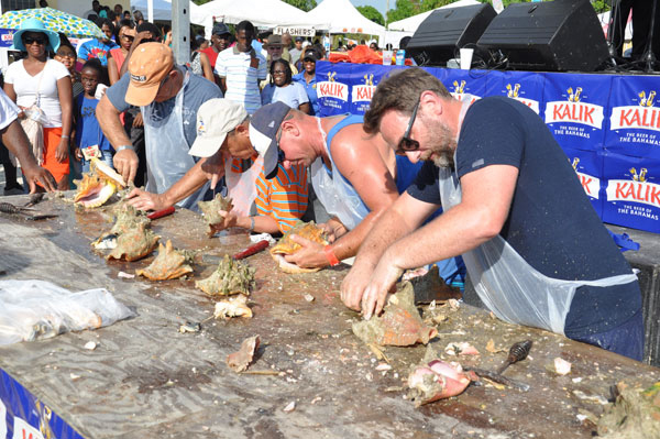VISITORS GET A TURN – Residents of Grand Bahama were not the only ones taking part in the 43rd annual Conch Cracking Competition. Shown are some of the visitors who did their best to remove the conch from the shells during the event on Monday in McLean's Town. (BIS Photo/Vandyke Hepburn)
