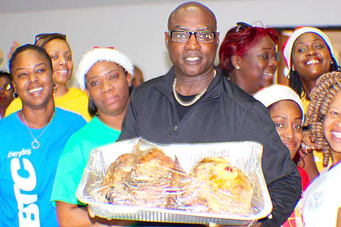 Chairman of the Kiwanis Give Love on Christmas Day Project, Barry Wilmott flanked by volunteers from the Bahamas Telecommunications Company.