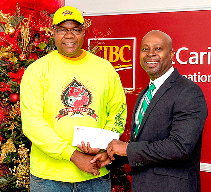 Sean Blyden CIBC FirstCaribbean Shirley Street Branch Manager presents a donation to Brian Adderley of Valley Boys, who were the winners of the Boxing Day Parade.