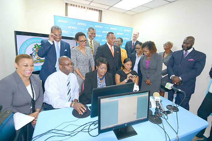 Incorporating companies online by computer, and smartphone at the E-Services Launch at Registrar General's Department, January 5, 2016. Looking on are Prime Minister Perry Christie, standing centre right; Attorney General Allyson Maynard Gibson, standing centre left; and Minister of Financial Services Hope Strachan, seated left. (BIS Photo/Peter Ramsay)