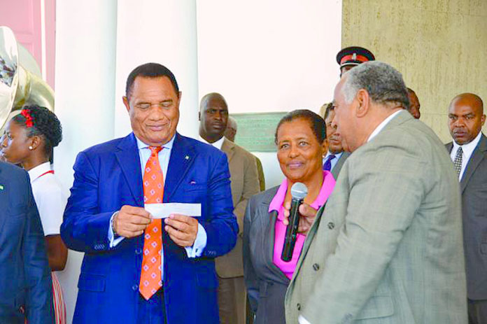 Prime Minister Christie receiving a $20,000 donation from the Wells family for work in the inner city in 2013.