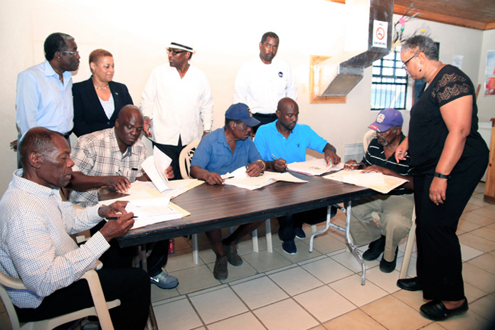 Melanie Roach of the National Repair and Reconstruction Unit oversees the signing of contracts awarded to contractors for repairs to Government buildings damaged during the passage of Hurricane Joaquin in October 2015. The contracts were signed Thursday, February 25, 2016. Pictured from left are contractors Julius Chisholm, Lionel Rolle, Curtis Hanna, Ivan Strachan and Marcel Collie-Moss. Standing from left are Harvey Roberts, Family Island Administrator, Acklins; the Hon. Hope Strachan, Minister of Financial Services, Investments and Local Government; the Hon. V. Alfred Gray, Minister of Agriculture and Marine Resource and MP for MICAL; and Captain Stephen Russell, Director, NEMA. (BIS Photo/Derek Smith)