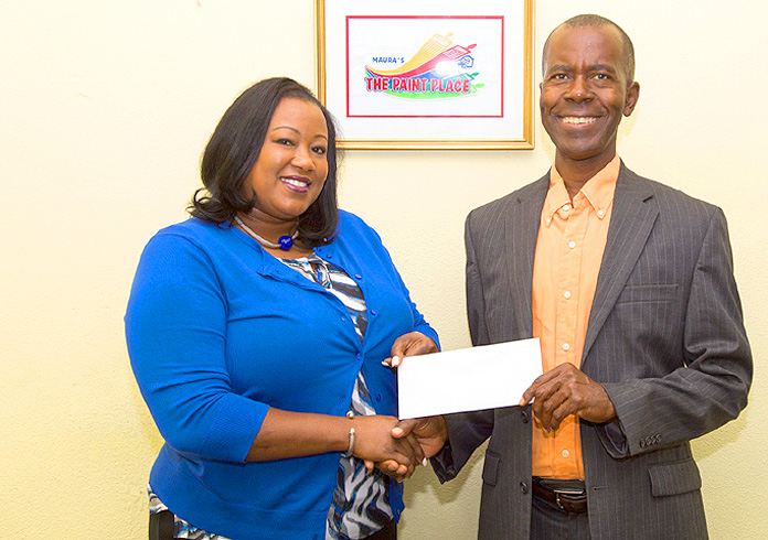 Christine King, General Manager at The Paint Place presents Philip Smith, Executive Director Bahamas National Feeding Network with a donation. (Photo by Cay Focus Photography.)