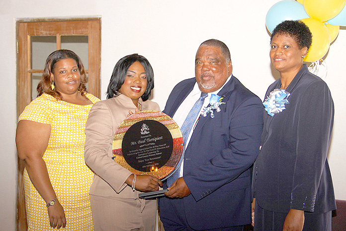 Retiring educator Paul Turnquest accepts a plaque from Mrs. Shenique Mackey-Paul, principal of the United Estates Primary School in San Salvador. He is flanked by Deborah Claridge and his wife Jacintha. (BIS Photo/Patrick Hanna)