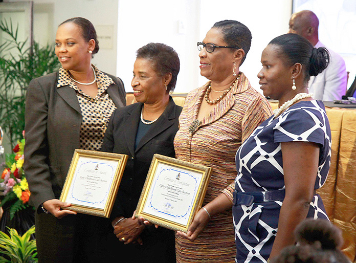 Dr. Pandora Johnson presents an award to the Early Childhood Care and Pre-School Section, MOEST, for its participation in the 2015 Commonwealth Good Practice Awards.