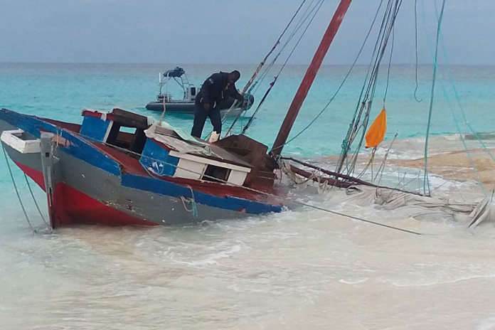 RBDF Marine searches wooden Haitian sailing sloop that beached on Half Moon Cay this morning.