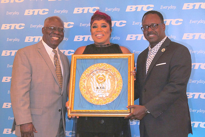 JCNP President Silbert Ferguson and Minister of Youth, Sports and Culture Danny Johnson present BTC, represented by Vice President of Marketing Eldri Ferguson-Mackey, with an award for their exemplary support.