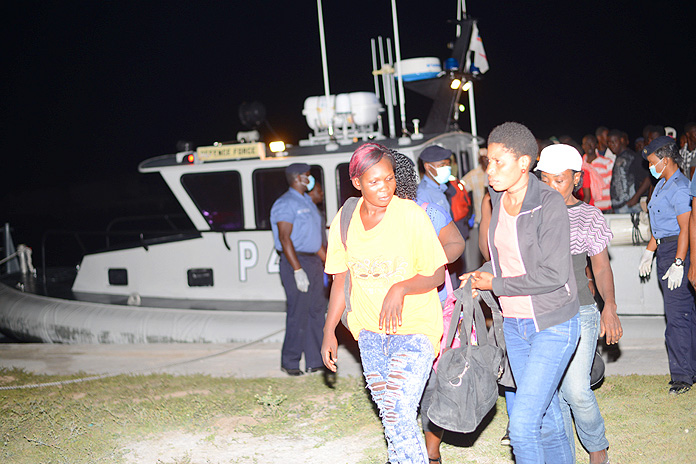 RBDF Marines assist migrants as they disembark HMBS P 44 upon arrival at HMBS Coral Harbour (Photo: Marine Seaman Stefan McDonald)