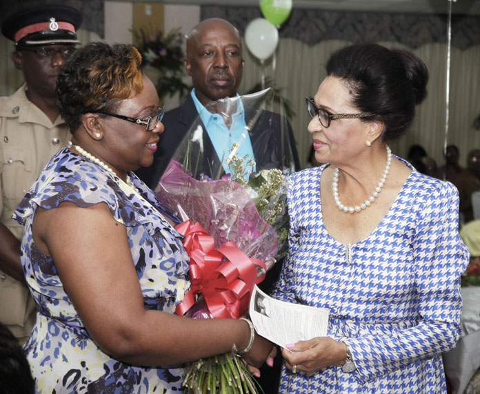 Mrs Gibson presents the Dame with flowers. Behind is Minister for Labour D. Shane Gibson.