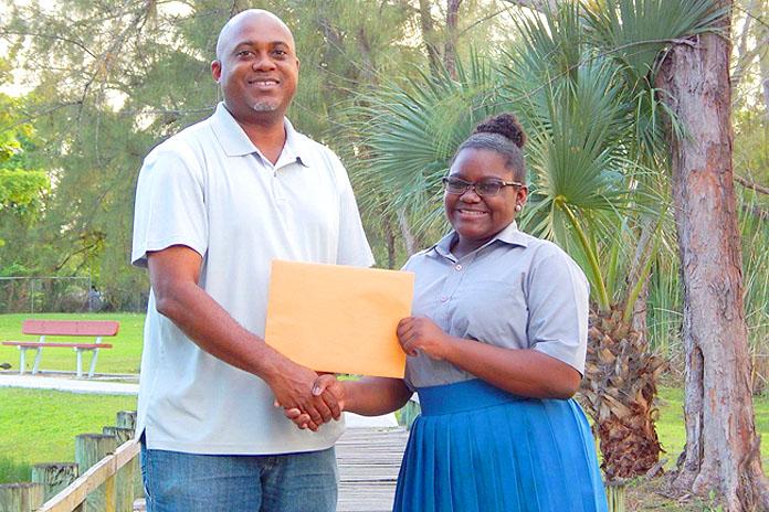 Pictured: Branae Minnis presenting her $2,000.00 Check to Mr. Vandyke Pratt, Foundation Chairman.