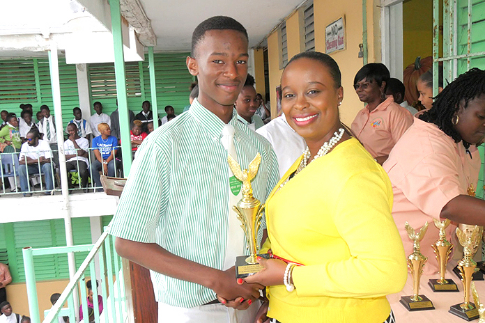 Indira Collie, BTC manager of public relations presents award of excellence to Head Boy Angelo Knowles
