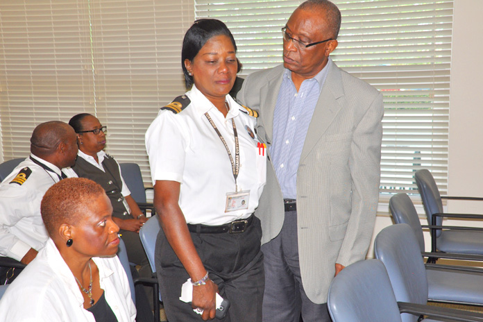 GRIEVING – Assistant Comptroller of Customs, Mr. Skerick Martin assists a grieving Elsa Neely. She was one of many officers, male and female, crying openly Friday as Mr. Martin spoke on the passing of Mr. Kevin Hanna who was reportedly shot by bandits at his South Bahamian home on Thursday afternoon. Also pictured seated is trained psychologist Dr. Pamela Mills.  (BIS Photo/Vandyke Hepburn)