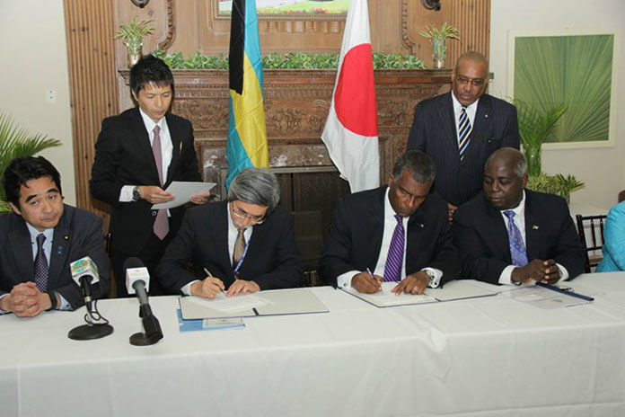 Pictured during the signing, seated from left: Mr. Manabu SAKAI, State Minister of Finance of Japan; Mr. Masanori NAKANO, Ambassador of Japan to the Commonwealth of The Bahamas; the Hon. Fred Mitchell, Minister of Foreign Affairs and Immigration, and the Hon. Philip Davis, Deputy Prime Minister and Minister of Works and Urban Development. Photos BELOW also show parties during handshake and a toast. (BIS Photos/Raymond A. Bethel, Sr.)