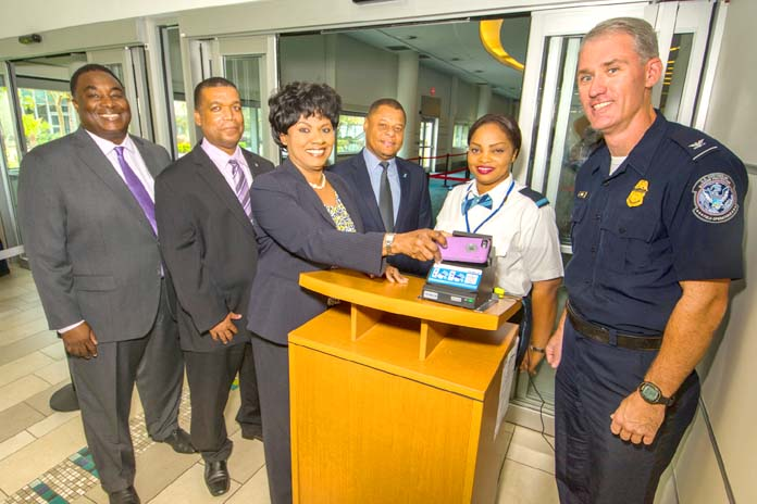 Airport CEO and partners launch the Electronic Boarding Pass system at Lynden Pindling International Airport (LPIA).  From left to right: Kevin McDonald, Vice President, Maintenance and Engineering, Nassau Airport Development Company Ltd. (NAD); Owen McKinney, Supervisor, Airport Authority; Vernice Walkine, President & CEO, NAD scanning her mobile device; Alan Sweeting, Chairman, Airline Operators Committee, LPIA; Alinka Rolle, Security Screener, Airport Authority; and Jeffrey Mara, Port Director, United States Customs and Border Protection.