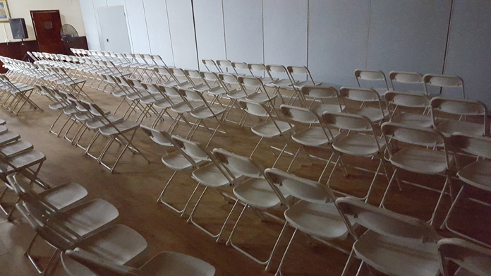Plenty chairs in the room partitioned off after few persons showed up.