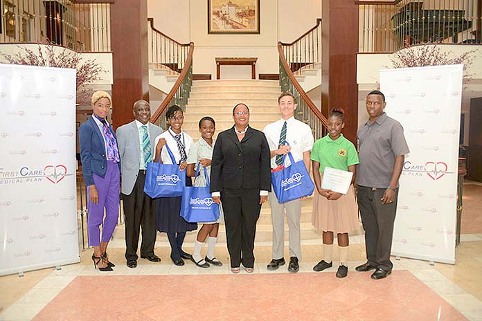 Essay Contest Winners Claim Prizes - Five students claimed prizes valued at more than $2k at the awards ceremony for the 4th Annual FirstCare Medical Plan Autism Awareness Essay Contest. Pictured left to right: Otishka Ferguson, Marketing Coordinator, Custom Computers; Lionel Sands, Director of Education, Ministry of Education, Science & Technology; Tyler Adderley, Second Runner-Up; Megan Lightbourne, First Runner-Up; Corinna Neely, President, FirstCare Medical Plan; Ethan Knowles, Grand Prize Winner; Rosheena Solace, Honourable Mention Winner; Rickcardo Miller, Acting President, REACH Bahamas.