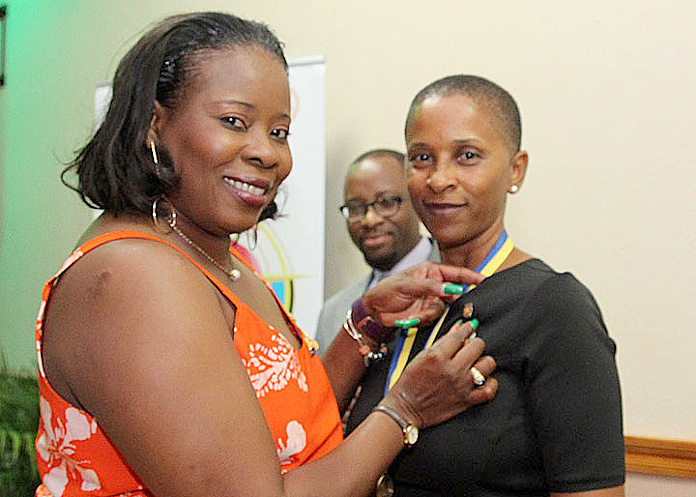 Immediate past president of the Rotary Club of South East Nassau, Dr Bridgette Rolle (left) transferred the president's medal and pinned incoming president (2016-2017) Lillian Russell (right), a lawyer and financial services professional. In the background is assistance district governor and past president of the Rotary Club of Nassau Sunrise, Mario Smith. IPP Bridgette joined the Rotary Club of South East Nassau in 2004 and President Lillian in 2002.