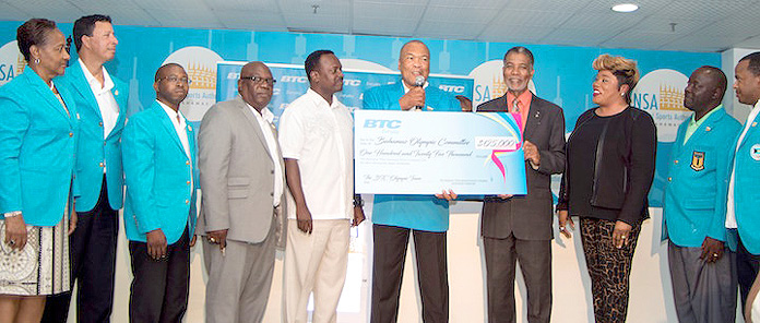 BTC Supports National Rio Olympic Team – Bahamas Olympic Committee President Wellington Miller (centre) receives a cheque for $125,000 to support the national Olympic team from Leon Williams, CEO of Bahamas Telecommunications Company, the team's major sponsor. Looking on is Minister of Youth, Sports & Culture Hon. Dr. Daniel Johnson MP (5th from left) and Team Chef de Mission Roy Colebrook (2nd from right) together with Olympic and BTC officials. BOC photo-Kevin Major
