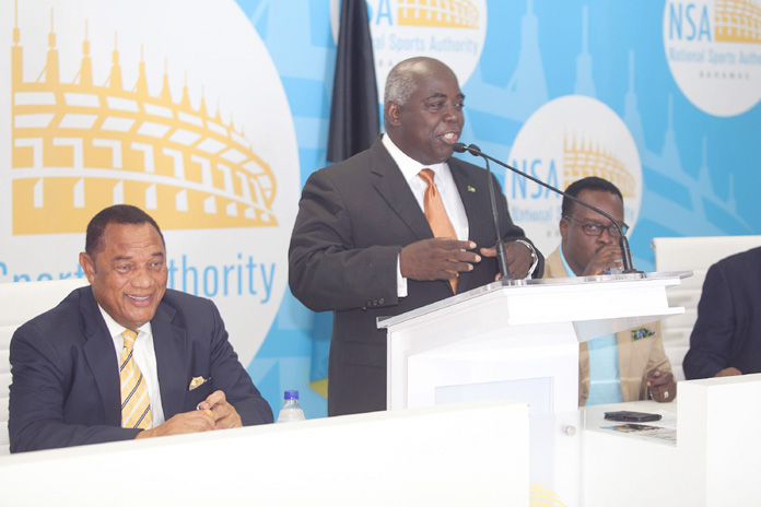 Minister of Works and Urban Development the Hon. Philip Davis, at podium, presents the plans for the Andre Rodgers National Baseball Stadium at the $21 million contract signing, July 18, 2016 at the Thomas A. Robinson National Stadium. Prime Minister and Minister of Finance the Rt. Hon. Perry Christie is at left; Minister of Youth, Sports and Culture the Hon. Dr. Daniel Johnson, at second right; and Permanent Secretary Calvin Balfour, at right. (BIS Photo/Derek Smith)
