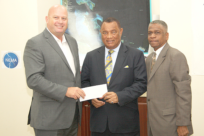 Exuma Developer $25,000 Donation – Children's Bay Cay and Williams Cay Project Manager Michel Neutelings, left, presents a cheque for $25,000 to Perry G. Christie, Prime Minister of The Bahamas, on behalf of developer Dona Bertarelli to assist with hurricane relief following the passage of Hurricane Matthew. On hand and assisting with the donation was Jack Thompson, Permanent Secretary, Office of the Prime Minister. Funds are earmarked for the National Reconstruction and Disaster Committee and for Rotary to supply survival kits. (Photo: Patrick Hanna, BIS)