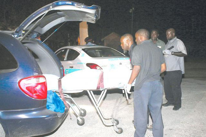 Morticians take away the body of a young girl caught in the gunfire of a gang shootout at the Sand Trap Bar on West Bays Street last evening. Photo by Nassau Guardian.