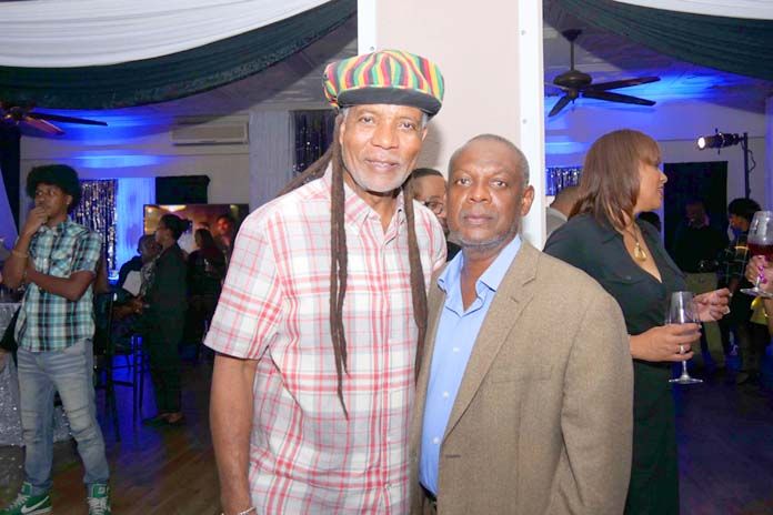"""BTC's CEO, Leon Williams channelling """"Bob Marley"""" and Kevin Basden, former General Manager of B.E.C. at the BTC 70's Inspired Corporate Event."""