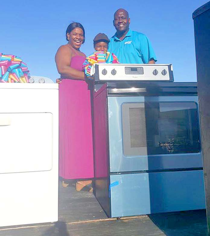 Ms. Ann Strachan is presented with a brand new stove courtesy of BTC.