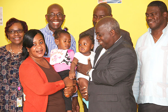 Deputy Prime Minister and Minister of Works and Urban Development the Hon. Philip Davis is pictured with the two toddlers presently enrolled in the Downtown Straw Market's new Day Care Centre. Also shown are representatives of the Straw Market Authority, including Chairman Kevin Simmons, third left. (BIS Photo/Patrick Hanna)